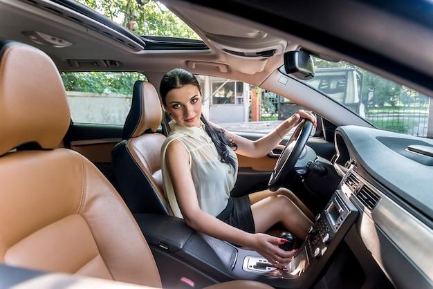 Beautiful brunette sitting in driver seat of car