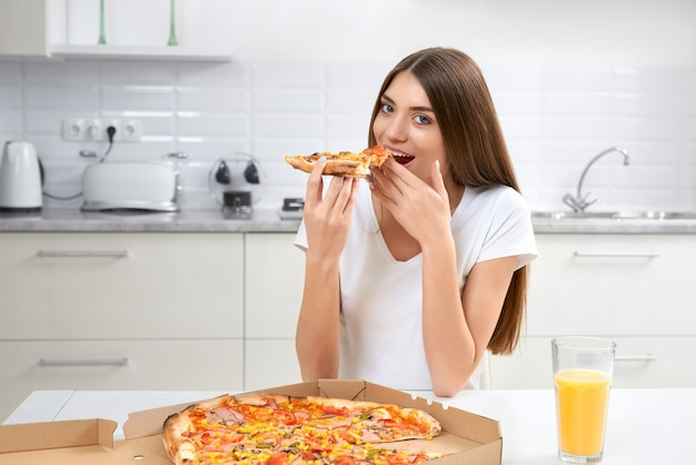 Beautiful brunette sitting in kitchen and eating pizza