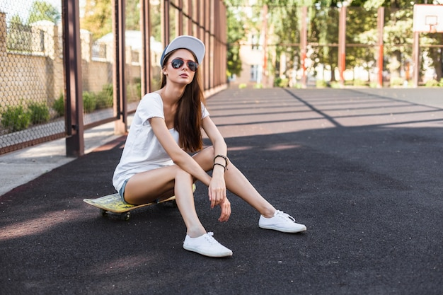 Beautiful brunette skater girl have fun on the playground urban style sitting on the skateboard