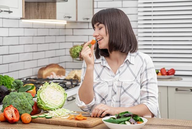 Bella bruna sorride e taglia le verdure su un'insalata sullo sfondo di un interno di cucina moderna.