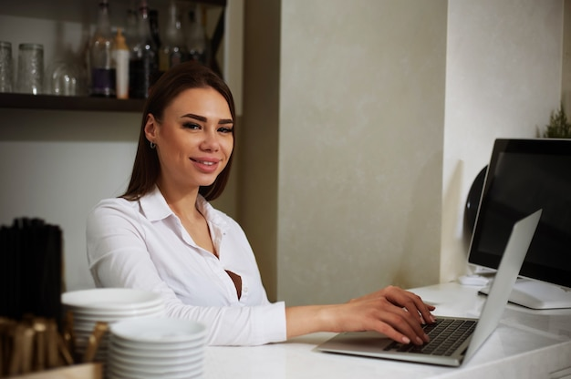 Beautiful brunette smiles at workplace, using her laptop