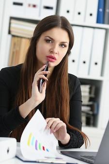 Красивая брюнетка улыбается бизнесвумен держать в руке мобильный телефон в офисе портрет на рабочем месте