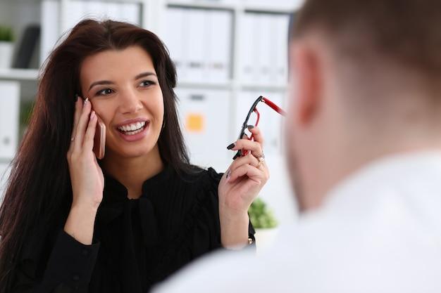 美しいブルネットの笑みを浮かべて実業家は、オフィスの肖像画で携帯電話を話します。