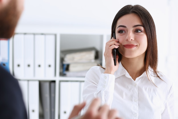 Beautiful brunette smiling businesswoman talk cellphone in office portrait. stay in touch negotiate meeting job white collar busy life style electronic device store professional training concept