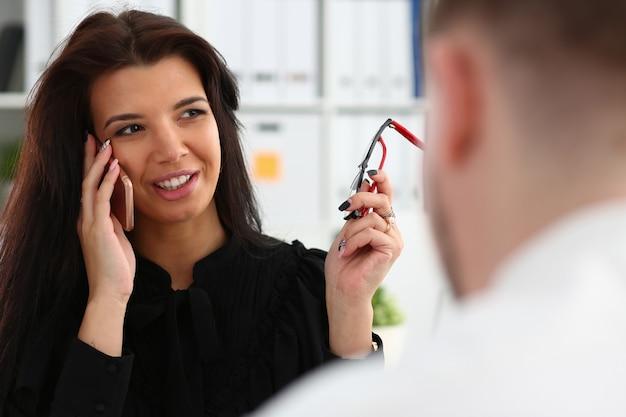 Красивая брюнетка улыбается бизнесвумен разговаривает по мобильному телефону