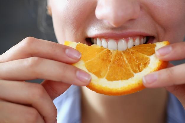 Beautiful brunette smiling woman eat sliced orange