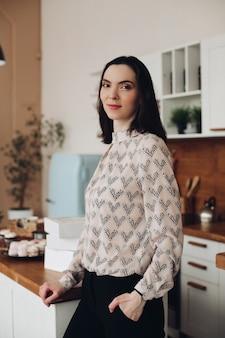 キッチンに立っている美しいブルネット。パターン化されたブラウスとダークパンツまたはジーンズがモダンなキッチンに立って、思慮深く目をそらしています。