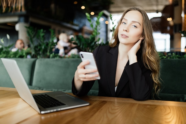 カフェでノートパソコンと携帯電話を使用して美しいブルネット。ブロガー作品コンセプト