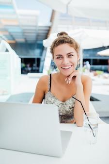 Bella bruna utilizzando laptop nella caffetteria all'aperto