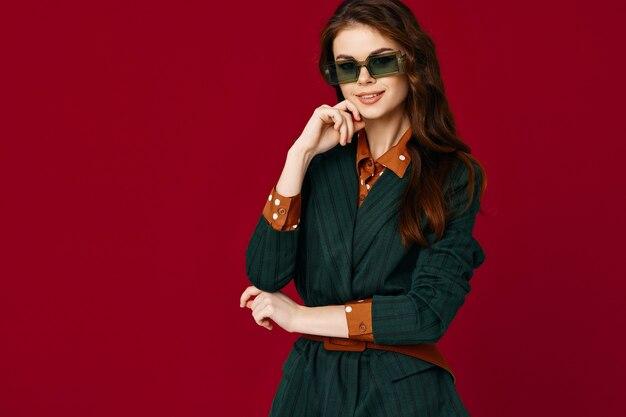 サングラスを身に着けている美しいブルネットは、ファッショナブルな服の赤い背景に合います