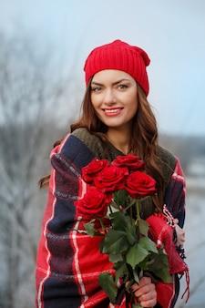 彼女の手に赤いバラの花束を持つ美しいブルネット