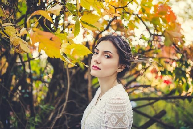 Красивая брюнетка с косами вокруг головы в стильной винтажной белой кружевной блузке с длинным рукавом в осеннем парке