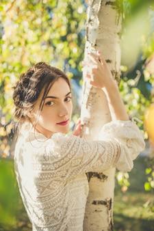 白樺の木の下でスタイリッシュなヴィンテージの白いレースの長袖ブラウスで頭の周りに三つ編みの美しいブルネット