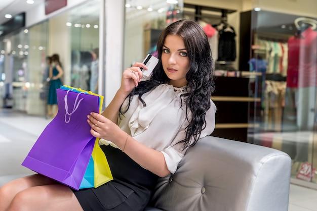クレジットカードとショッピングバッグの美しいブルネット