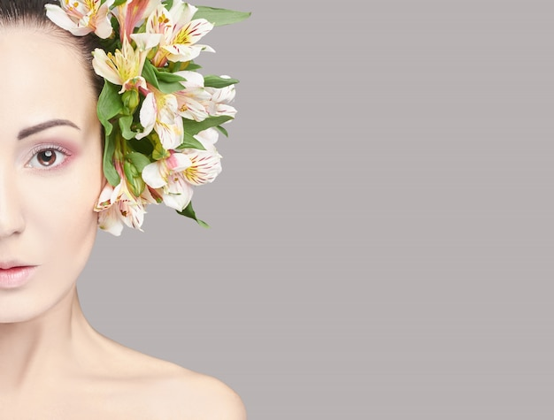 Beautiful brunette with flowers on his head makeup
