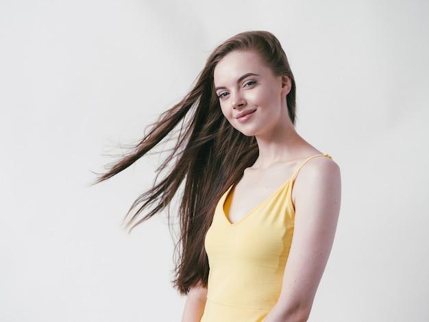 Красивая брюнетка с длинными гладкими волосами в желтой рубашке естественный портрет на белом фоне