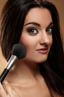 Beautiful brunette with makeup brush