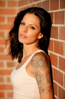 Beautiful brunette with red brick wall of background