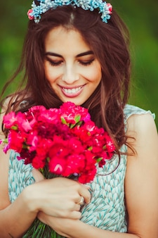 Beautiful brunette with red flowers in her arms