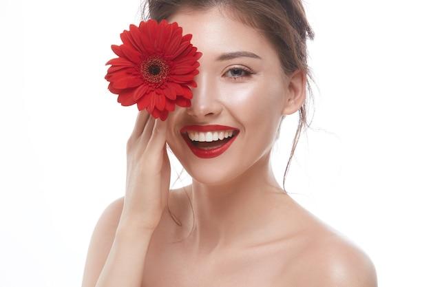 赤い唇と大きな花がカメラに微笑んで彼女の片目を閉じる美しいブルネット