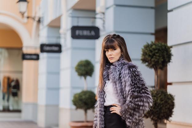 灰色の毛皮のコート、白いシャツ、黒のスカートに身を包んだ長いストレートの髪と美しいブルネット