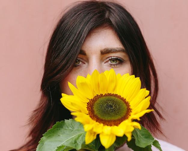 Beautiful brunette with yellow sunflower