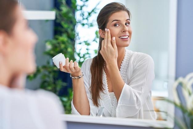 浴室でフェイスクリームを適用する美しいブルネットの女性
