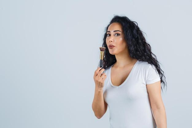 Beautiful brunette woman applying makeup