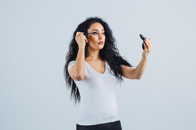化粧を適用する美しいブルネットの女性
