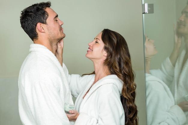 Beautiful brunette woman applying moisturizer on man's face