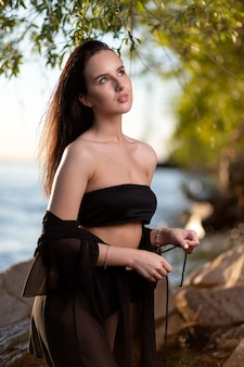 A beautiful brunette woman in a black swimsuit and a light cape-shirt is resting on the beach . pretty skinny girl at sea beach