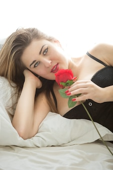 Beautiful brunette woman in bra posing with red rose