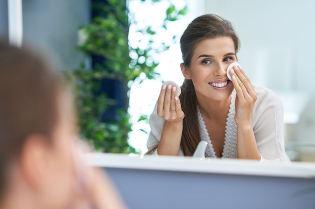 아름 다운 갈색 머리 여자 화장실에서 얼굴을 청소