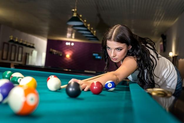 Красивая брюнетка женщина сосредоточилась на бильярдной игре
