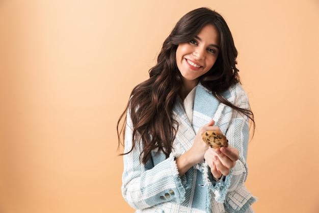 ベージュの上に孤立して立っている格子縞のジャケットに身を包んだ美しいブルネットの女性、カメラにクッキーを与える