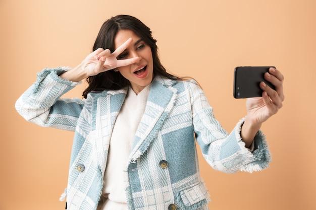 Красивая брюнетка женщина, одетая в клетчатую куртку, стоя изолированную над бежевым, делает селфи с мобильным телефоном