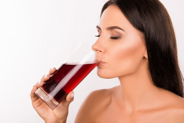 チェリージュースを飲む美しいブルネットの女性