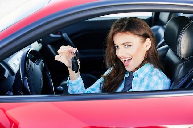 赤い車を運転し、自動車を購入する美しいブルネットの女性。新しい自動車の幸せな所有者、カメラを見て、笑顔で、キーを保持しています。頭と肩、幸せなドライバー