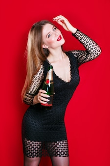 Beautiful brunette woman in evening dress smiling and looking, holding champagne