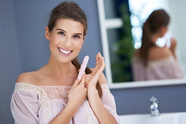 浴室で釘をファイリングする美しいブルネットの女性