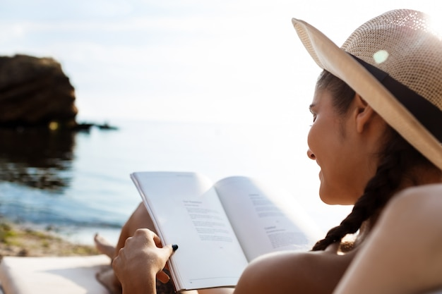Beautiful brunette woman in hat reading book, lying at beach