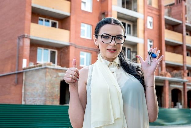 新しいアパートから鍵を保持している美しいブルネットの女性