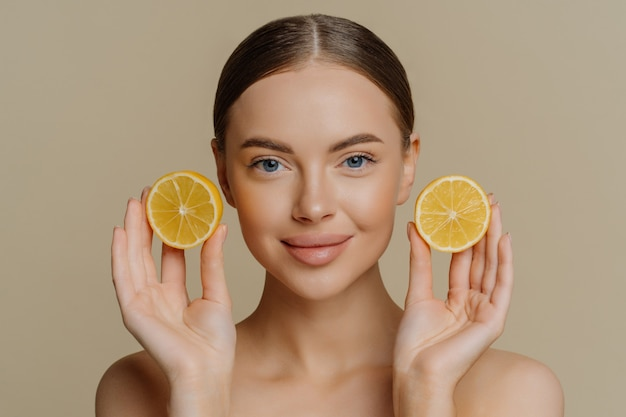 Beautiful brunette woman holds juicy lemon slices has healthy shiny skin gets vitamins from citrus