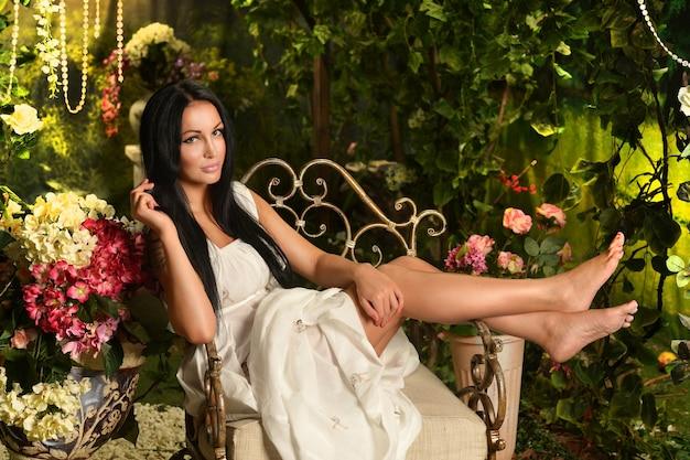 긴 흰색 드레스를 입고 의자에 앉아 꽃 장식 근처에서 포즈를 취하는 아름다운 갈색 머리 여자