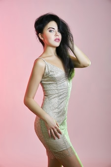 ピンクの背景に短いイブニングドレスの美しいブルネットの女性