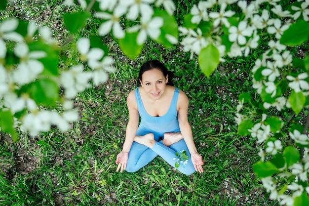 푸른 잔디에 앉아 요가 휴식, 명상 개념을 하는 꽃이 만발한 봄 나무의 배경에 스포티한 파란색 정장을 입은 아름다운 브루네트 여성.