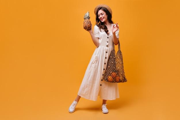 ストリングバッグにパイナップルと果物でポーズをとるカンカン帽と綿のドレスの美しいブルネットの女性。