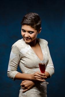 Красивая брюнетка женщина в вечернем платье, улыбаясь, держа бокал