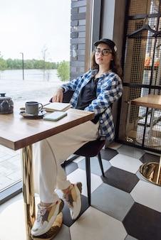 세련된 옷 카탈로그에 있는 레스토랑에서 포즈를 취하는 안경을 쓴 아름다운 갈색 머리 여자