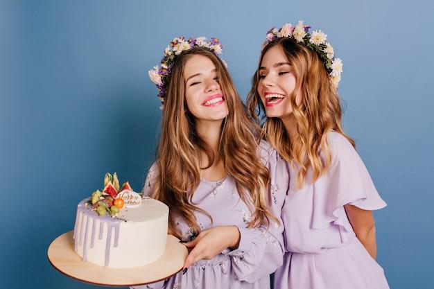 Красивая брюнетка женщина в фиолетовом платье держит торт ко дню рождения